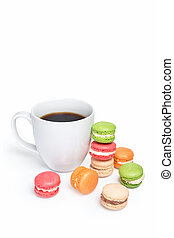 Sweet and colorful macaroons with cup of coffee on white background. Traditional french dessert macarons, space for text.