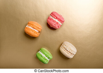 Sweet and colourful macaroons on golden background. Traditional french dessert. Copy space.