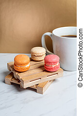 Sweet and colourful macaroons served on little wooden pallets with cup of coffee on a marble texture table and golden background. Traditional french dessert. Copy space.