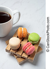 Sweet and colourful macaroons served on little wooden pallets with cup of coffee on a marble texture background. Traditional french dessert. Copy space