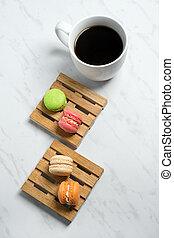 Sweet and colourful macaroons served on little wooden pallets with cup of coffee on a marble texture background. Traditional french dessert.