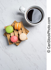 Sweet and colourful macaroons served on little wooden pallets with cup of coffee on a marble texture background. Traditional french dessert. Top view, copy space