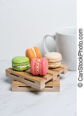 Sweet and colourful macaroons served on little wooden pallets with cup of coffee on a marble texture background. Traditional french dessert. Copy space.