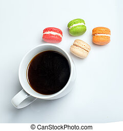 Sweet and colourful macaroons with cup of coffee on white background. Traditional french dessert. Top view, flat lay, space for text