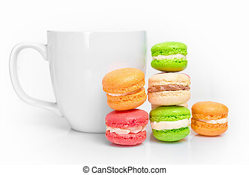 Sweet and colourful macaroons with cup of coffee on white background. Traditional french dessert.