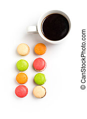 Sweet and colourful macaroons with cup of coffee on white background. Traditional french dessert. Copy space.