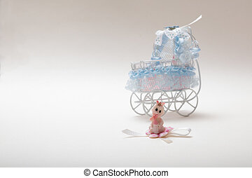 Sweet baby doll sitting in front of a baby carriage isolated on white with copy space