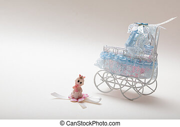 Sweet baby doll sitting in front of a miniature baby carriage isolated on white with copy space