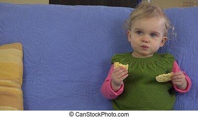 sweet baby girl eat biscuit sit on blue sofa in room. 4K -...