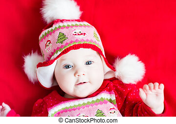 Sweet baby girl in a Christmas knitted dress and hat
