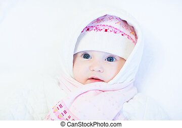 Sweet baby girl in a knitted hat and scarf on white background