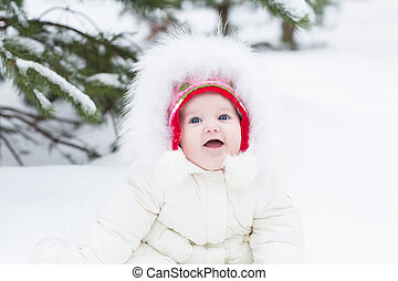 Sweet baby girl in a white jacket sitting under a snowy christmas tree