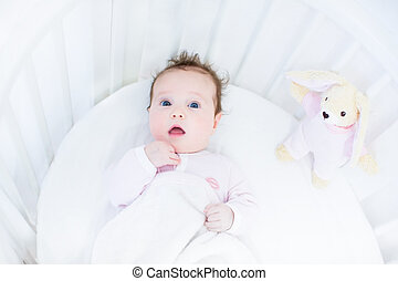 Sweet baby girl in a white round crib with pink bunny toy