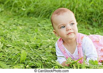 Sweet baby girl lying on grass