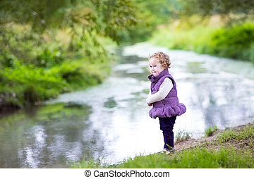 Sweet baby girl playing at a river shore in an autumn park