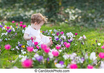 Sweet baby girl playing in a field of flowers