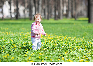 Sweet baby girl playing in a sunny spring park