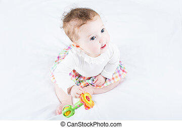 Sweet baby girl playing with a toy sitting on a white blanket