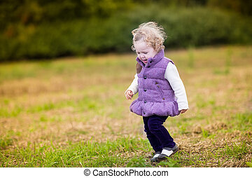 Sweet baby girl running in a colorful autumn park