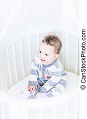 Sweet baby girl sitting in a round white bassinet