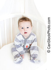 Sweet baby girl sitting in a white round crib