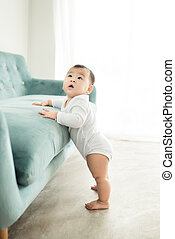 Sweet baby girl standing by the sofa at home.