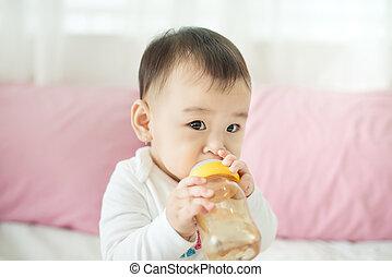 Sweet baby girl sucking milk in bottle at home.