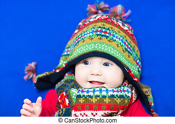 Sweet baby in a knitted colorful hat and scarf on a blue blanket
