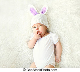 Sweet baby in knitted hat with a rabbit ears lying on bed, top view