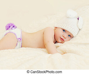 Sweet baby in knitted hat with a rabbit ears lying on bed