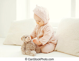 sweet baby playing with teddy bear toy at home in white room near window