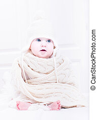 Sweet baby sitting in a white nursery in a huge hat and knitted scarf