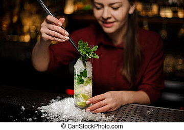 barmaid completes the design of the mojito alcohol cocktail