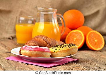 Sweet breakfast, donuts, oranges and orange juice on wooden table