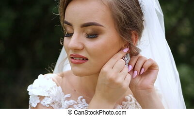 Sweet bride with a beautiful hair pulls on the earring.