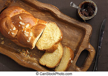 Sweet brioche bread on tray with knife and marmalade