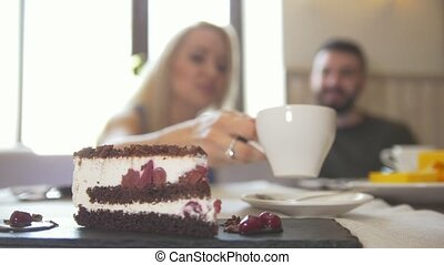 Sweet cake in front of couple sitting in a cafe enjoying...