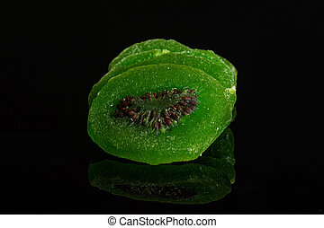 Sweet candied kiwifruit isolated on black glass