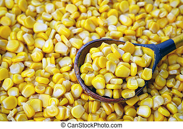 sweet canned corn in a wooden spoon