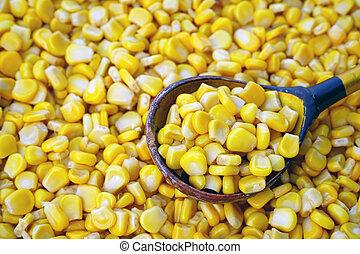 sweet canned corn in a wooden spoon