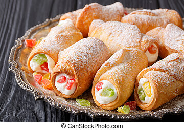 sweet cannoli stuffed with cheese cream and candied fruits close-up on a plate. horizontal