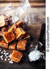 Sweet caramel candies.  Salted caramel pieces and sea salt close up.