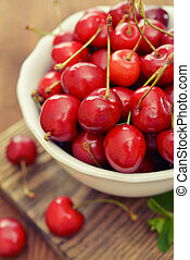 Sweet cherries - Fresh sweet cherries in bowl on wooden...