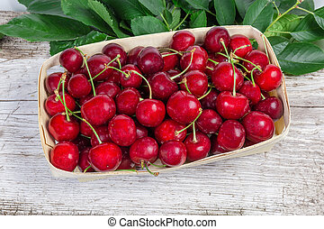 Sweet cherries in basket, leaves on the old wooden surface