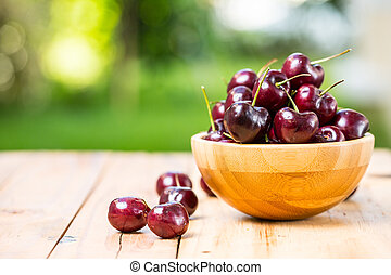 Sweet cherries on the table in garden.