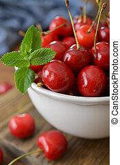 Sweet cherries - Fresh sweet cherries in bowl on wooden...