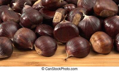 Sweet chestnut on wooden table, Castanea sativa fall food,...