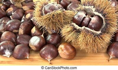 Sweet chestnut on wooden table with calybium, Castanea...