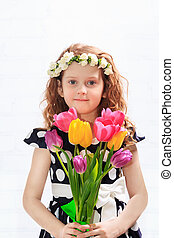 Sweet child with bouquet of tulips.