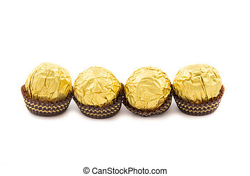 Sweet chocolate balls with almond wrapped in gold foil paper on white background